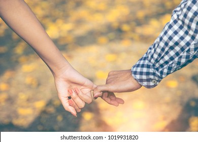 Close up of two Lovers Joining Hands. Detail Silhouette of Man and Woman holding hands over the Yellow flowers fall to the ground. Background. Couple Trust, Love and Happiness concept.Valentine