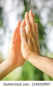 Close up of two male hands give high five sign outdoors