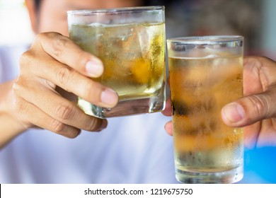 Close up two men clinking glasses of whiskey drinking alcoholic beverage together.