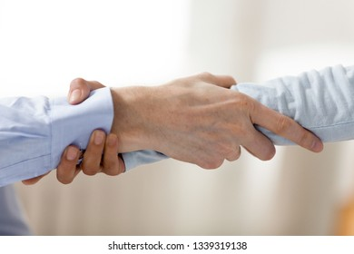 Close up two men holding each other wrist. Rescuing, helping gesture of two hands. Two business people handshake as sign of support. People at work. Business assistance concept. Couple hold each other