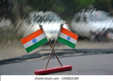 Close up of two miniature Indian national flag made of paper small metal stand crossing each other on the top of a car dash board in background  water falling down the wind screen, selective focusing