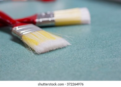 Close up of two paint brush on green table