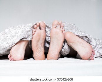 Close up of two people feet in a bed.