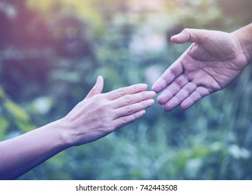 close up of Two people touch hands each other over blurred nature background,Business man and woman shaking hands,helping hand and world peace concept. Vintage tone with copy space