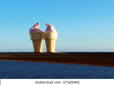 Close up of two pink ice cream cone desserts resting on railing of cruise ship in blue calm sea. The cones are touching each other evoking feeling of romance.