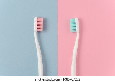 Close up of two plastic white toothbrushes with pink and blue bristle on pink and blue background. Free copy space.