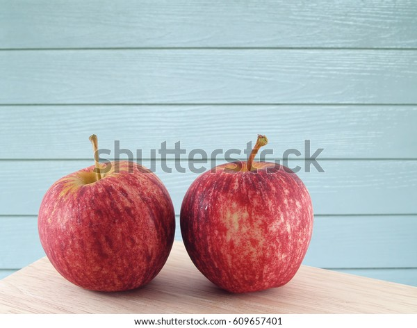 close up two red apples with water droplets on wooden kitchen table and blue wood paneling wall background, round shape fruit used as dessert or ingredients of salad or making cider and juice