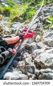 Close up of two red locking carabiners being pushed up along a steel wire by a male hand with cutout gloves, on a via ferrata route section in Baia de Fier, Gorj county, Romania.