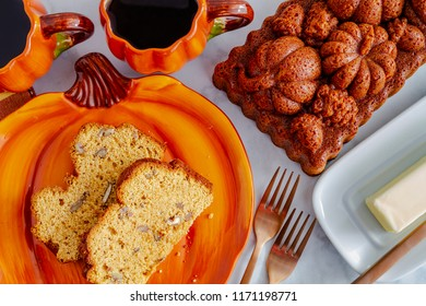 Close up of two slices of pecan pumpkin bread sitting on pumpkin plate with two cups of coffee and a whole loaf of bread