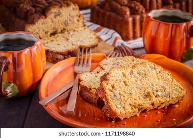 Close up of two slices of pecan pumpkin bread slices sitting on pumpkin plate with two cups of coffee and fresh baked loaves of bread