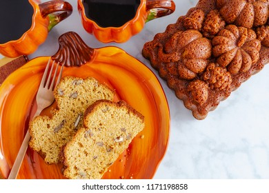Close up of two slices of pumpkin bread sitting on pumpkin plate with two cups of coffee and a whole loaf of bread made in decorative pan with space for text