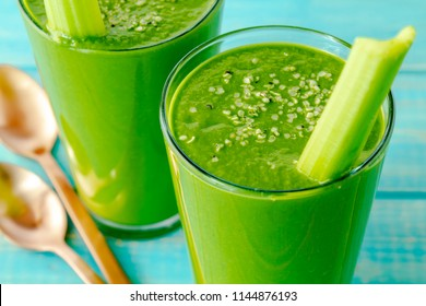 Close up of two tall glasses filled with kale and spinach green juice drink garnished with celery stalks and hemp seeds with two copper spoons on side