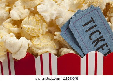 close up of two tickets stubs in a box of popcorn. Concept of movie time.