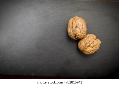 Close up of two walnuts on a black slate background, testicle concept could be used for a testicular cancer advert