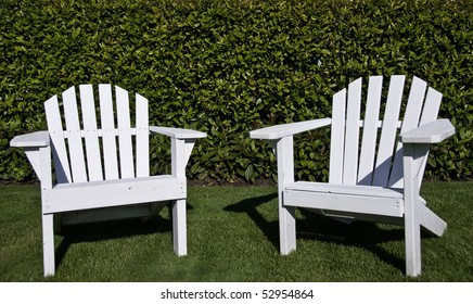 Close up of two white adrindack chair on a lawn.