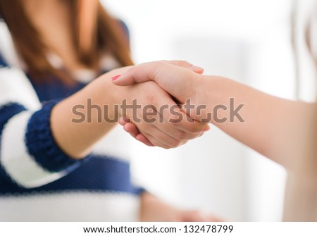 Close Up Of Two Women Shaking Hands, Indoors
