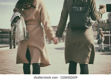 Close - up of two women walking the streets of the city holding hands, retro toning
