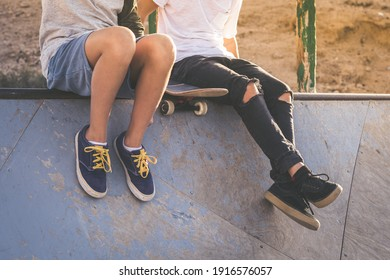 Close up of two young boys sitting on half pipe ramp, after nice tricks and jumps at the skatepark. Trendy teenagers enjoying free time at the skate park. Youth, togetherness and friendship concept.