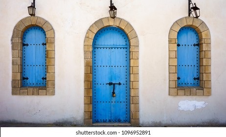 Close up of typical blue door and windows in Morocco on white background.