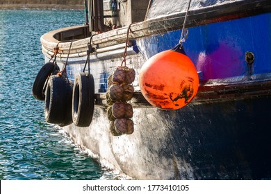 Close up of tyres and buoys hanging from wooden fishing boat in golden hour