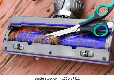 close up of the under side of a vacuum cleaner with har wrapped around the brushes creating a common problem