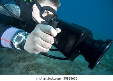 Close up of an underwater camerman filming in crystal clear water. MORE INFO: Model released