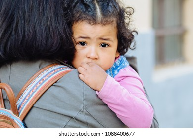 Close up of unhappy dark skinned toddler baby girl crying while her unrecognizable ecuadorian mother trying to calming down and holding her on hands. No to violence against children concept.