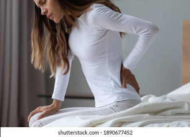 Close up unhappy woman wearing pajama rubbing stiff back muscles after awakening, sitting on bed, upset young female feeling pain, incorrect posture or uncomfortable bed, backache after sleep