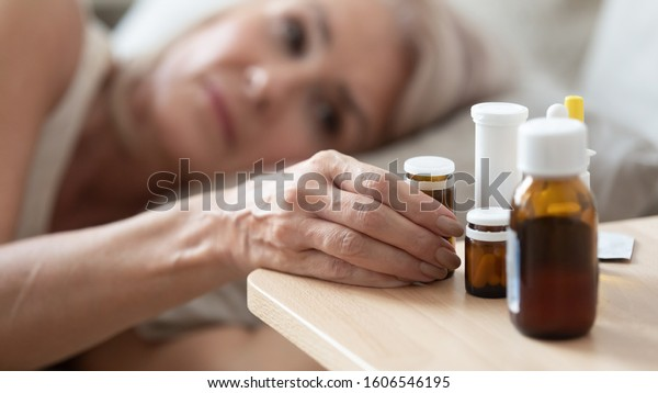 Close up of unhealthy mature woman lying in bed feel sick take medicines from bedside table to relieve symptoms, ill lonely senior female having meds pills suffer from flu, elderly healthcare concept