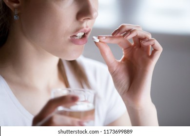 Close up of unhealthy woman feel unwell taking pill from headache or pain, female have painkiller or antibiotic medicine, girl hold glass of water and antidepressant suffering from depression