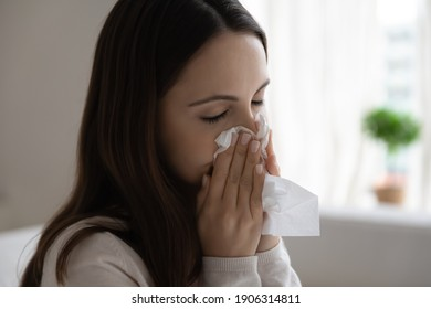 Close up of unhealthy young Caucasian woman blow in napkin suffer from flu or cold. Unwell sick millennial female snuffle struggle with virus symptoms, have runny nose. Corona, covid-19 concept.