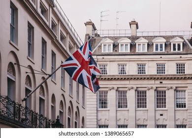 Close up of a Union Jack British flag flowing in the wind, on a pole outside a building in London, UK.