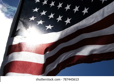 Close up of a United States Flag outside in the sun. Detail of the stars on blue background of the American flag waving in the wind. Looking at the sun through a US flag, noise/film grain filter added