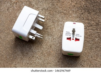 Close up of universal electric socket plug adapters used for travel. Used to connect to different electrical outlets worldwide. Electric adapter isolated on dark background.