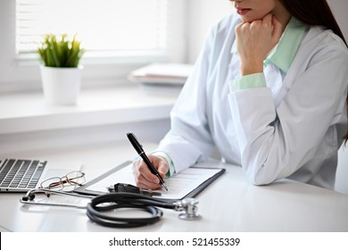 Close up of  unknown female doctor sitting  at the table near the window in hospital and typing at laptop computer
