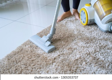 Close up of unknown woman using a vacuum cleaner while cleaning carpet in the house