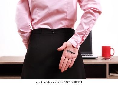 Close up of unknown young woman back showing #Metoo hashtag word on palm. Me too movement. Cry for help. Hostile office environment. Anti sexism protest against inappropriate behavior towards women.