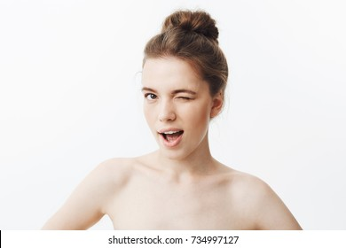 Close up of unny young girl with brown long hair in bun hairstyle and skinny body type, being half naked, holding hands on waist, winking, smiling, looking in camera with flirty expression.