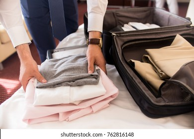 Close up of unrecognizable businessman packing suitcase for business trip folding clothes on hotel bed