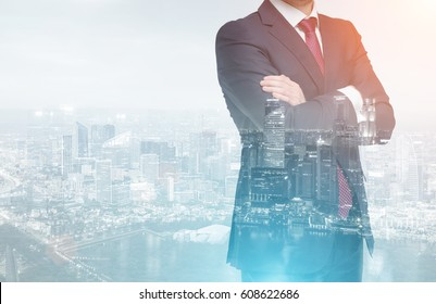 Close up of an unrecognizable businessman standing with his arms crossed against a city panorama. Double exposure. Toned image