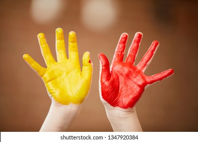 Close up of unrecognizable child showing hands colored with paint, finger painting and creativity concept , copy space