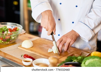 Close up of unrecognizable cook cutting onions and other vegetables with chef knife while working in modern kitchen, copy space