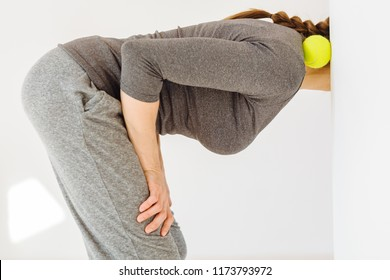 Close up of unrecognizable female in gray sportswear doing self-massage technique applying tennis ball for back pain relief, working out leaning angle of wall in pilates studio white background.