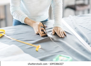 Close up of unrecognizable female tailor cutting fabric with scissors while sewing custom made clothes, copy space