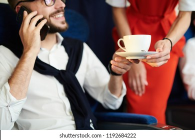 Close up of unrecognizable flight attendant serving cup of coffee to handsome man sitting in first class and enjoying flight, copy space