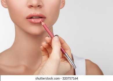 Close up of unrecognizable pretty girl getting her lips painted. The female hand of visagiste is holding a pencil and drawing lips. Isolated