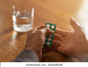 Close up of unrecognizable senior person taking aspirin with glass of water