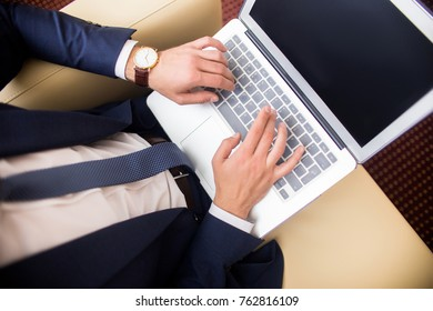 Close up of unrecognizable successful businessman using laptop working with Internet in hotel room or lobby, copy space