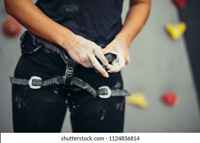 Close up of unrecognizable woman arranging harness on her waist in climbing gym. Climbing equipment on sporty femaale body.