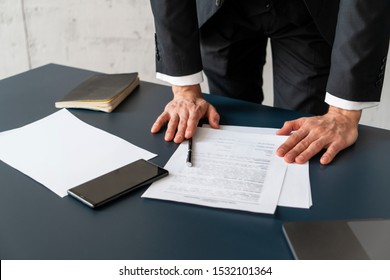 Close up of unrecognizable young businessman standing at office table and reading contract. Concept of corporate lifestyle